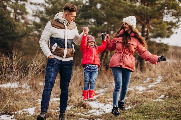 Família jovem caminhando juntos na floresta no inverno Foto gratuita