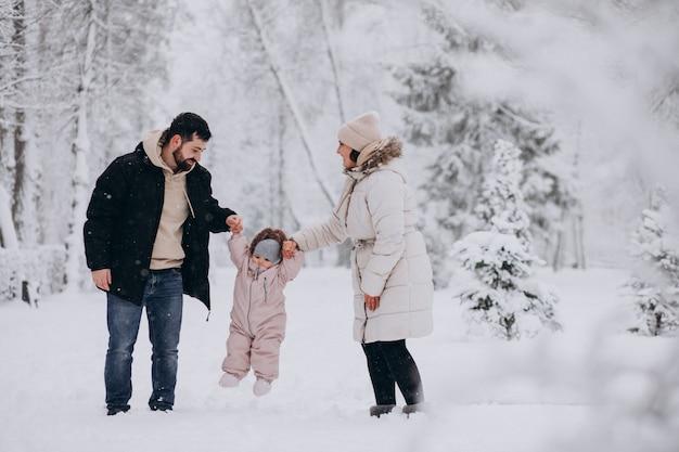 Família jovem com filha em uma floresta de inverno cheia de neve Foto gratuita