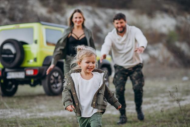 Família jovem com filha parada na floresta Foto gratuita