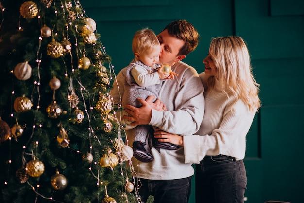 Família jovem com filha pendurar brinquedos na árvore de natal Foto gratuita