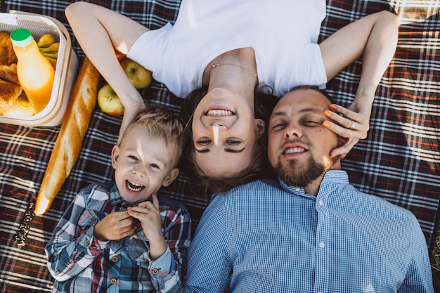 Família jovem com filho pequeno fazendo piquenique no parque Foto gratuita