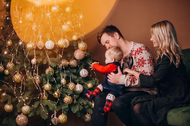 Família jovem com menina sentada perto de árvore de natal Foto gratuita