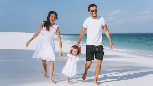 Família jovem com pouco daugher em um período de férias pelo oceano Foto gratuita