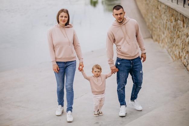 Família jovem, com, seu, pequeno, criança bebê, em, parque, por, a, lago Foto gratuita