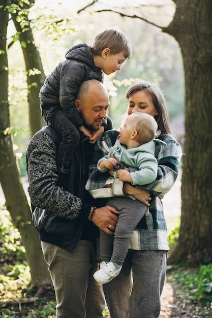 Família jovem com seus filhos se divertindo na floresta Foto gratuita