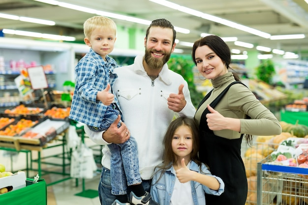 Família jovem com um filho e filha em um supermercado. Foto Premium