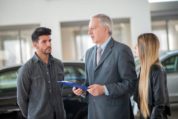 Família jovem conversando com o vendedor e escolhendo seu novo carro em um showroom Foto Premium