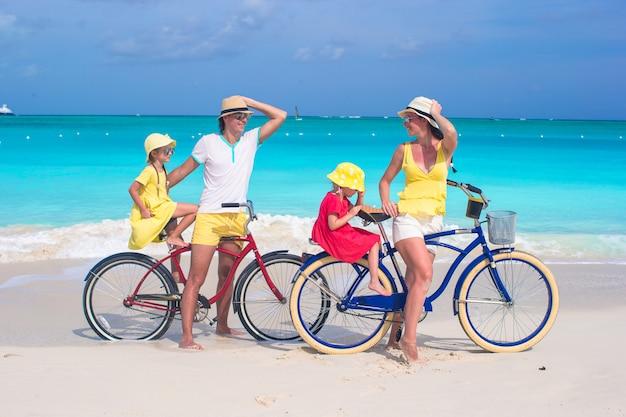 Família jovem de quatro andar de bicicleta na praia de areia tropical Foto Premium