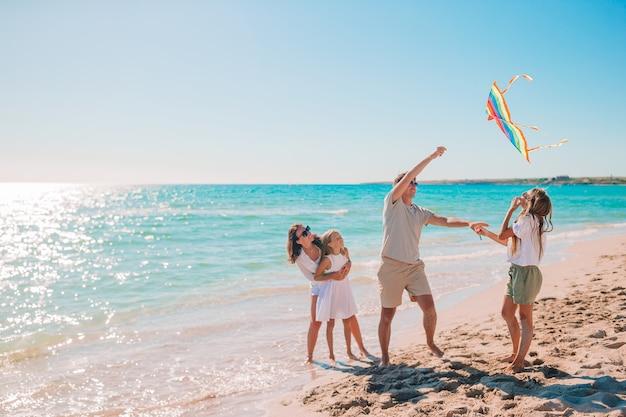 Família jovem e feliz com dois filhos empinando pipa na praia Foto Premium