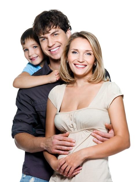 Família jovem e feliz com uma criança bonita posando no espaço em branco Foto gratuita
