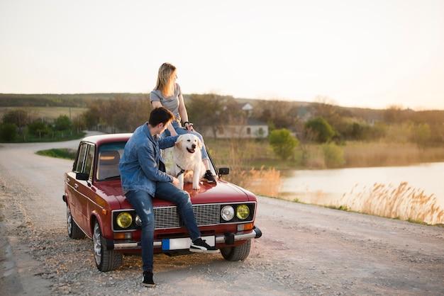 Família jovem em uma viagem com seu cachorro Foto gratuita