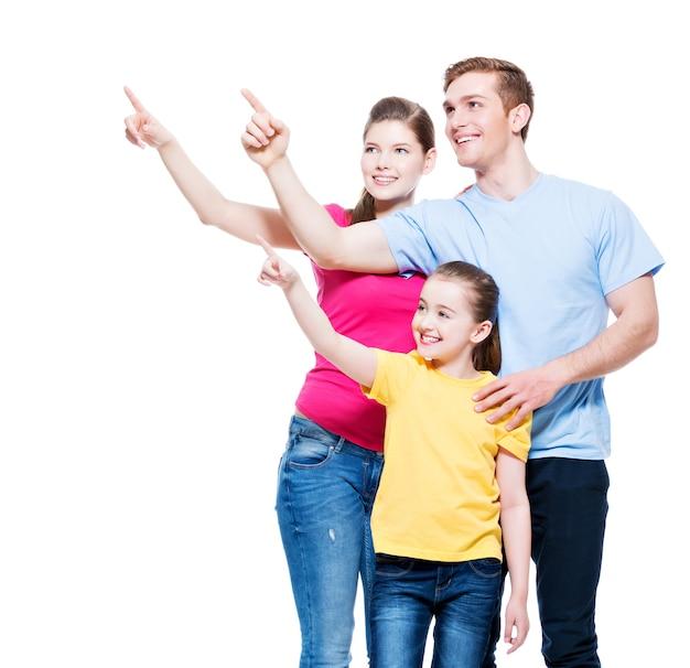 Família jovem feliz com criança apontando o dedo para cima - isolada na parede branca Foto gratuita