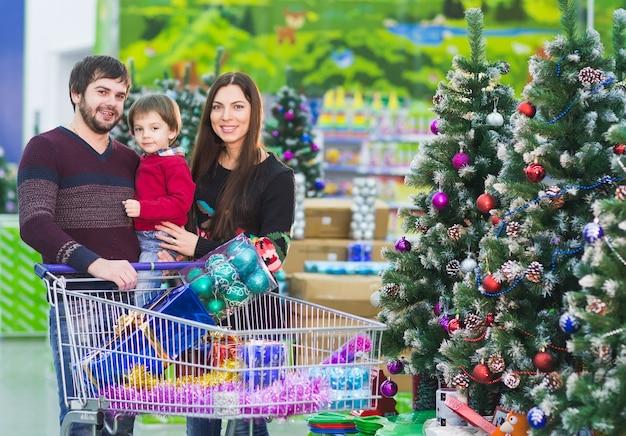 Família jovem feliz no supermercado escolhe presentes para o natal Foto Premium