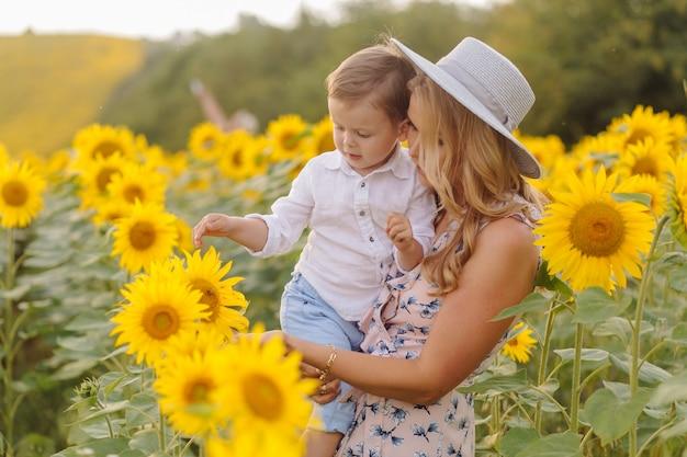 Família jovem feliz, pai mãe e filho, estão sorrindo, segurando e abraçando no campo de girassol Foto gratuita