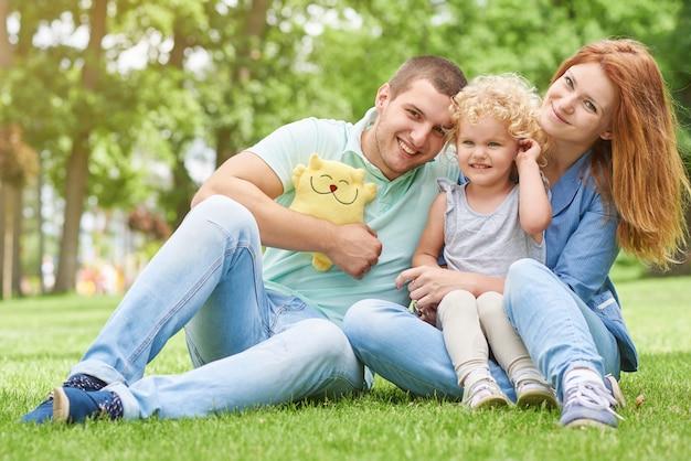 Família jovem feliz relaxante no parque Foto Premium