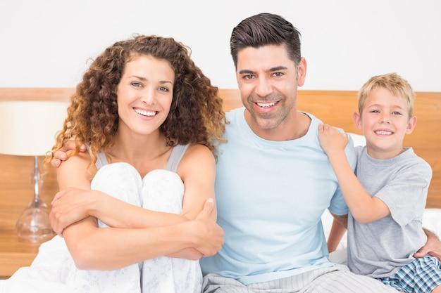 Família jovem feliz sorrindo para a câmera na cama Foto Premium
