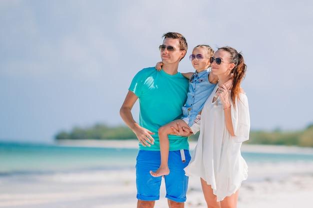 Família jovem na praia branca durante as férias de verão Foto Premium