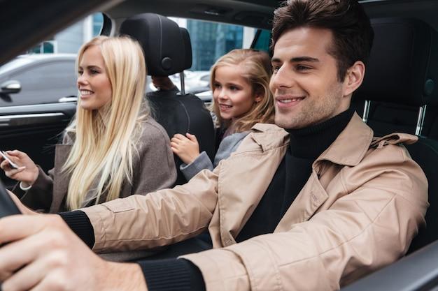 Família jovem sorridente, sentado no carro Foto gratuita