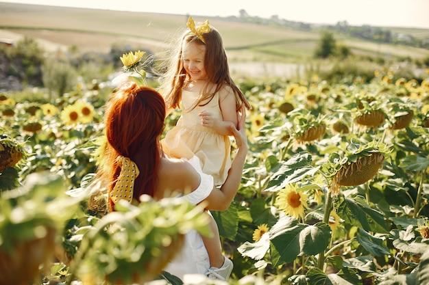Família linda e fofa em um campo com girassóis Foto gratuita