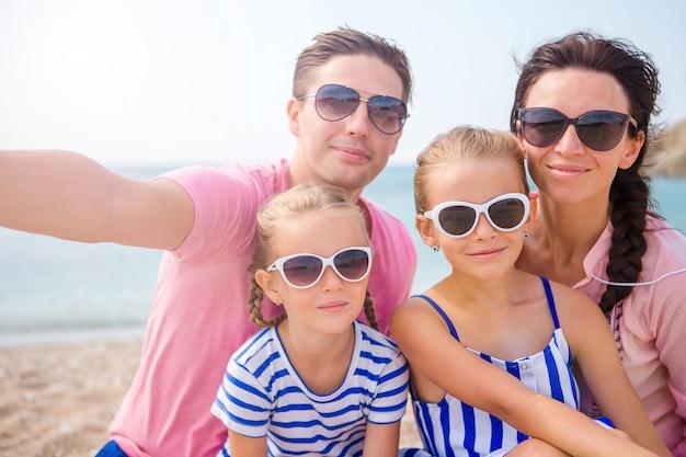 Família linda jovem tomando selfie na praia Foto Premium