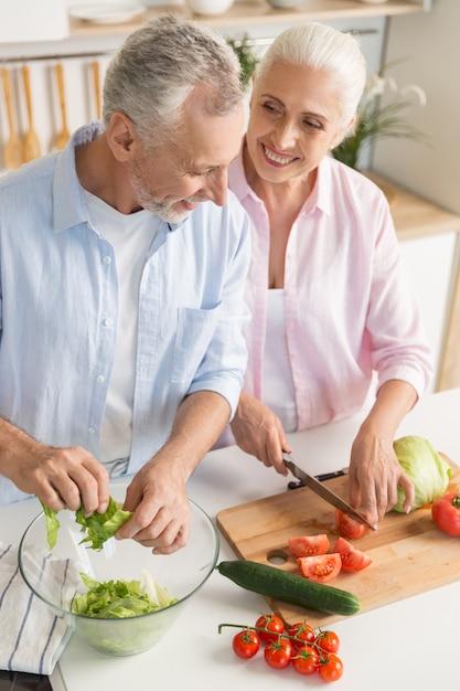 Família madura madura feliz casal cozinhar salada Foto gratuita