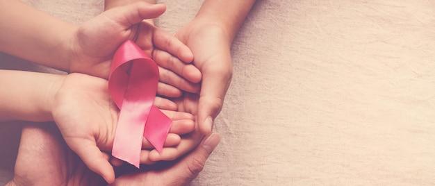 Família mãos segurando uma fita rosa, conscientização do câncer de mama, rosa de outubro Foto Premium
