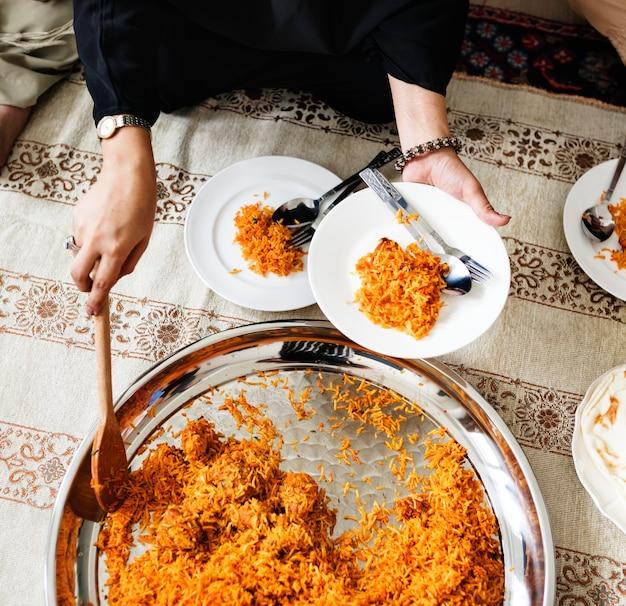 Família muçulmana jantando no chão Foto gratuita