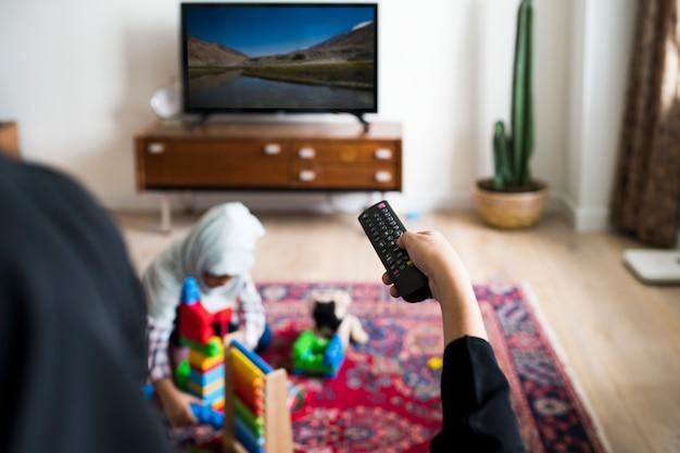 Família muçulmana relaxar e brincar em casa Foto Premium