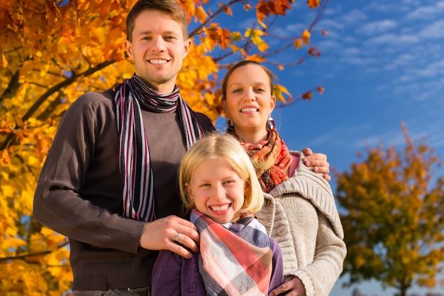 Família na frente de árvores coloridas no outono ou Foto Premium