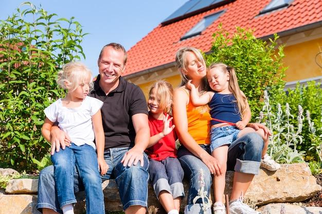 Família na frente de casa ou casa Foto Premium