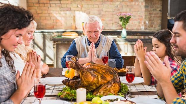 Família na mesa rezando antes de comer Foto gratuita