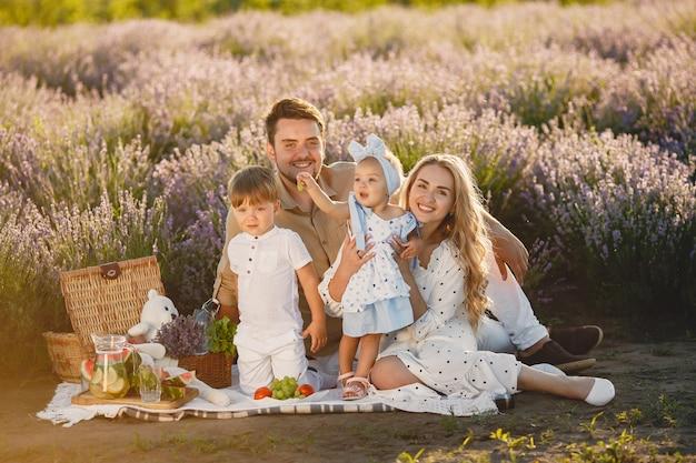 Família no campo de lavanda. pessoas em um piquenique. mãe com filhos come frutas. Foto gratuita