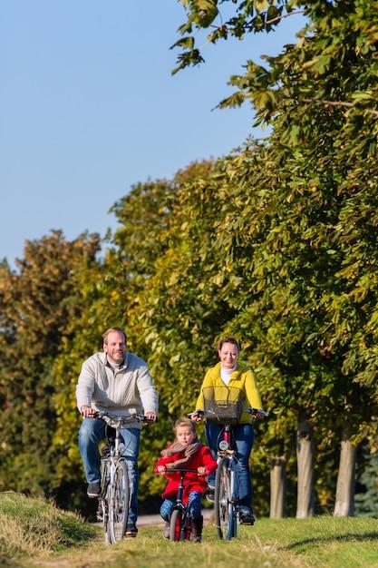 Família no passeio de bicicleta no parque Foto Premium