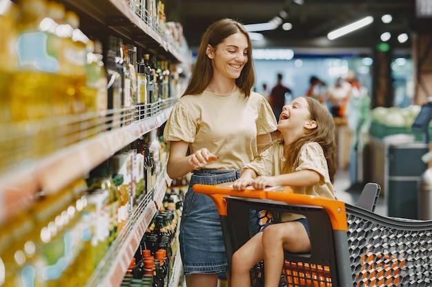 Família no supermercado. mulher em uma camiseta marrom. as pessoas escolhem produtos. mãe com filha. Foto gratuita