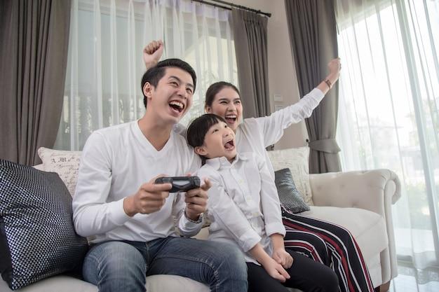 Família nova que joga videogames junto em casa e que tem o divertimento junto. Foto Premium