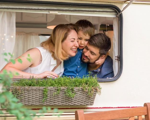 Família olhando pela janela de um trailer Foto gratuita