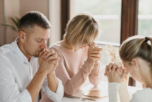 Família orando junta antes de comer em casa Foto gratuita