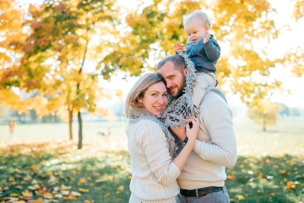 Família par abraçando no parque ao ar livre com seu bebê sentado nos ombros do pai Foto Premium