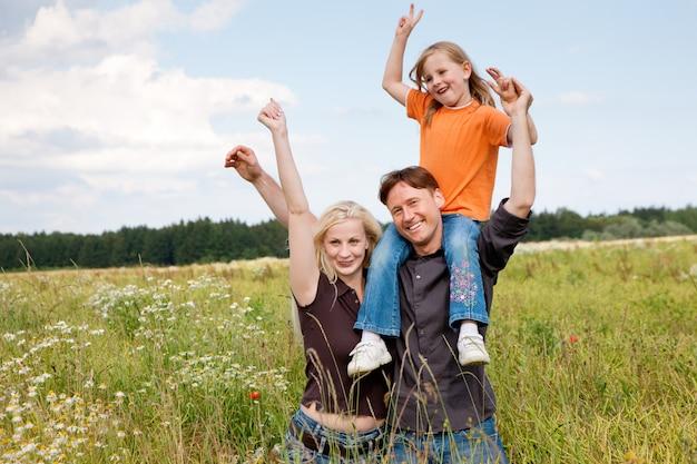 Família posando em um campo de grama Foto Premium