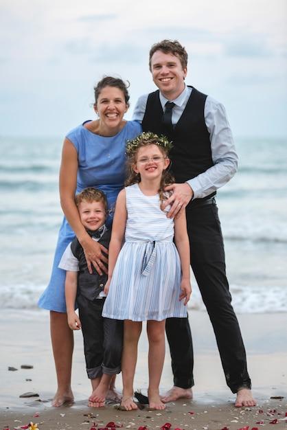 Família posando para uma foto de grupo na praia Foto Premium