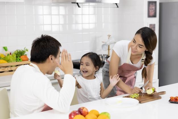 Família preparando a refeição na cozinha Foto Premium