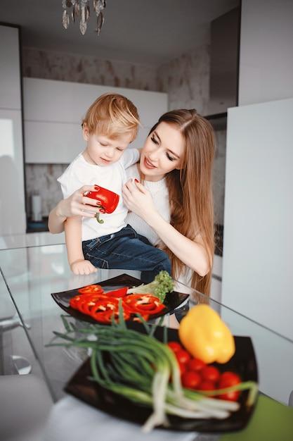 Família preparar a salada em uma cozinha Foto gratuita