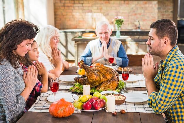 Família rezando antes das refeições Foto gratuita