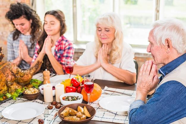 Família rezando antes de comer Foto gratuita