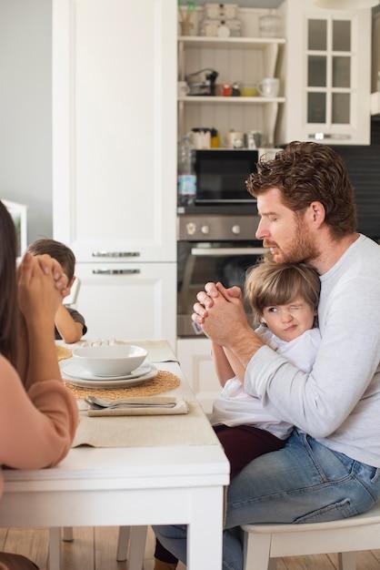 Família rezando juntos em casa Foto gratuita