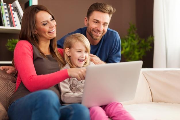 Família rindo junta e usando laptop em casa Foto gratuita