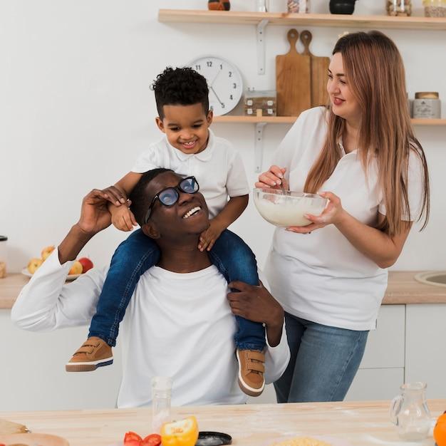 Família se divertindo ao fazer um pouco de comida na cozinha Foto gratuita