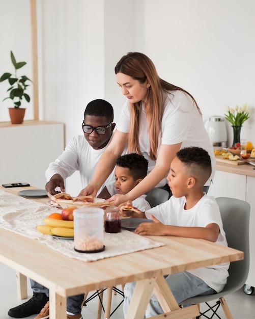 Família se preparando para comer pizza Foto gratuita