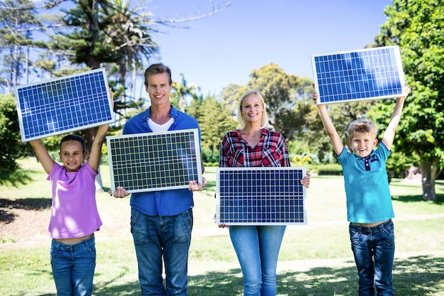 Família segurando um painel solar Foto Premium