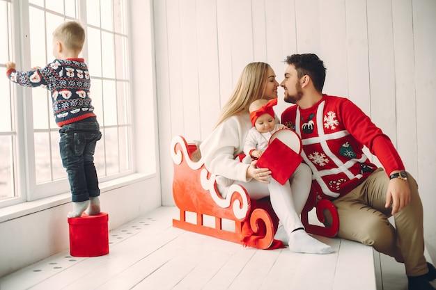Família sentada em casa com presentes de natal Foto gratuita